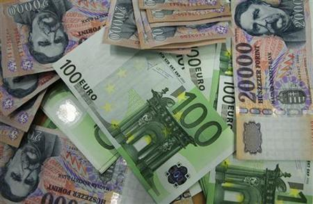 An illustration picture shows a Hungarian Forint and Euro banknotes displayed in OTP bank in Budapest