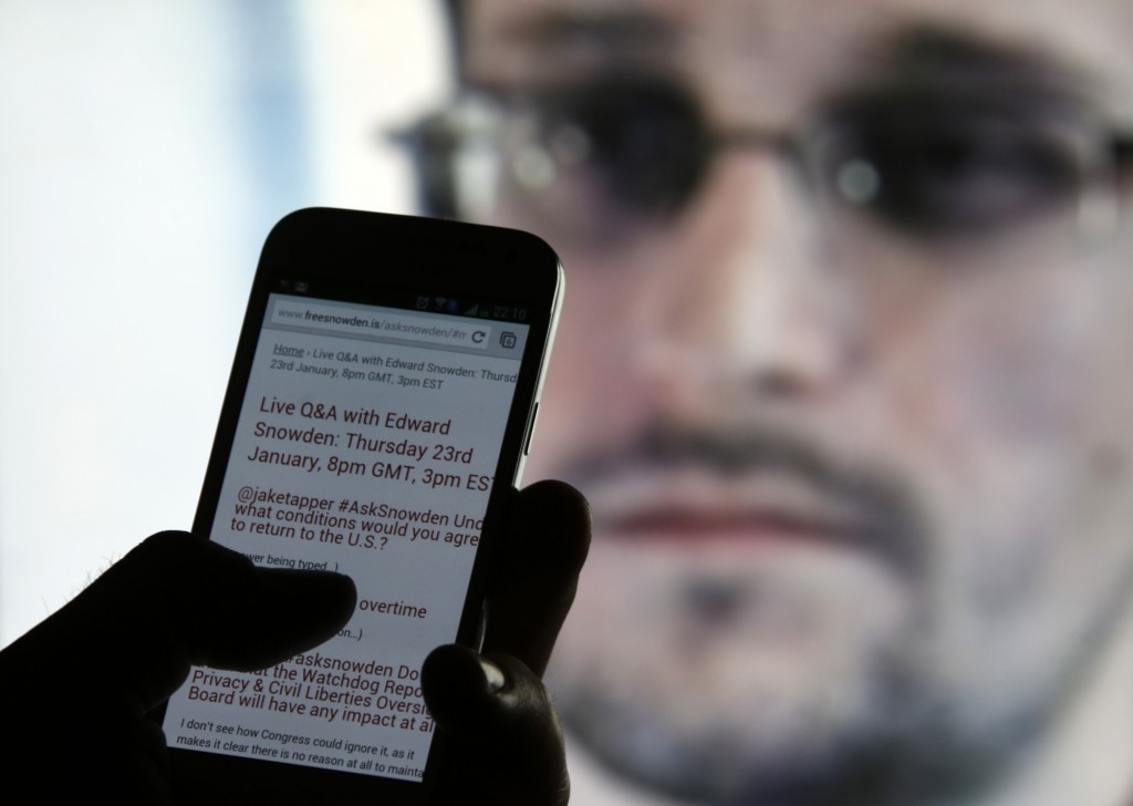 Photo illustration of man using phone to read about Edward Snowden answering users' questions, in Sarajevo