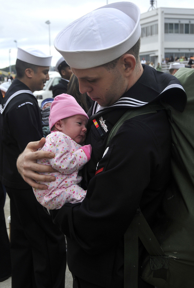 Sailor-Matthew-Sandlin-holds-his-newborn-daughter.