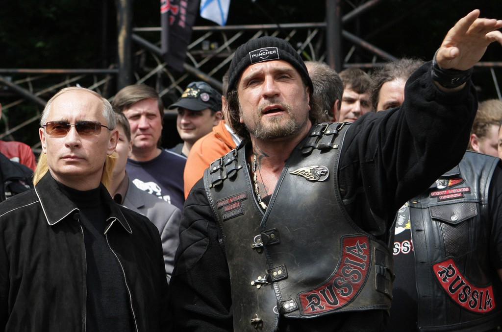 "A picture taken on July 7, 2009, shows Vladimir Putin (L), then Russian Prime Minister, listening to the leader of Nochniye Volki (the Night Wolves) biker group, Alexander Zaldostanov (R), also known as Khirurg (the Surgeon), during Putin's visit to the ""Night Wolves"" biker club's  headquarters. AFP PHOTO / RIA NOVOSTI / POOL / ALEXEY DRUZHININ"