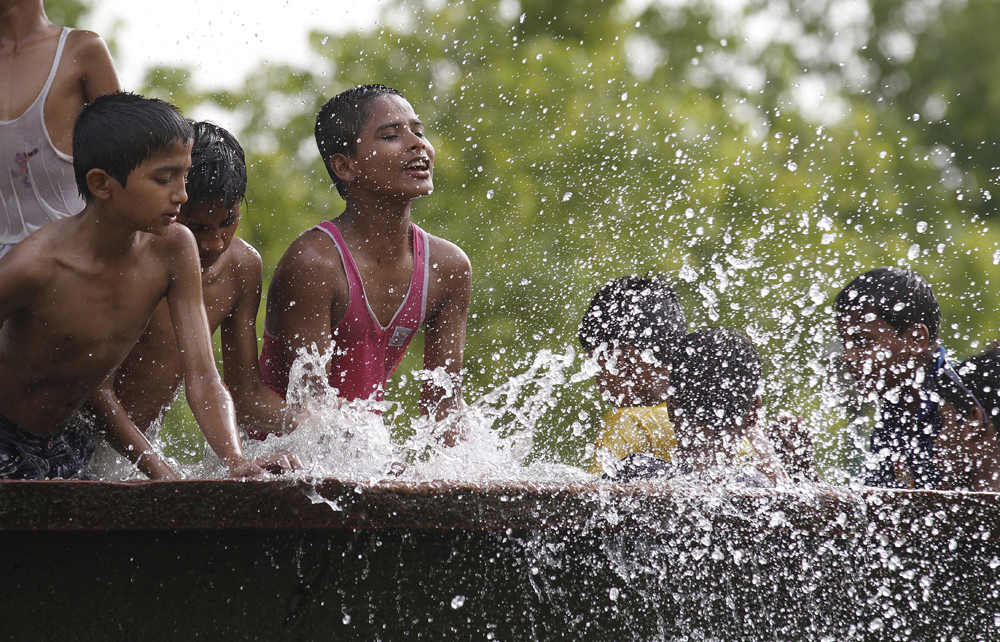 NEW DELHI, INDIA - MAY 24: Children enjoying at India Gate water pond during a hot weather as Delhi/NCR experienced yet another scorching day, on May 24, 2015 in New Delhi, India. The national capital sizzling today as heat wave-like conditions prevailed across the city with mercury hovering above 44.7 degree Celsius, making life tough for the Delhiites. (Photo by Virendra Singh Gosain/Hindustan Times via Getty Images)