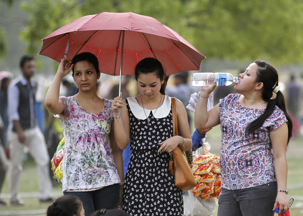 NEW DELHI, INDIA - MAY 24: Delhiites protect themselves during a hot weather as Delhi/NCR experienced yet another scorching day, on May 24, 2015 in New Delhi, India. The national capital sizzling today as heat wave-like conditions prevailed across the city with mercury hovering above 44.7 degree Celsius, making life tough for the Delhiites. (Photo by Virendra Singh Gosain/Hindustan Times via Getty Images)
