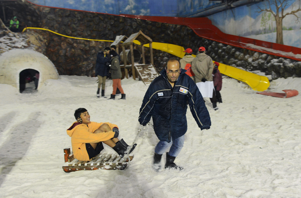 Indian visitors play on a sledge at the snow park, which generates artificial snow inside a specialised enclosure, at the Maniar Wonderland theme park on the outskirts of Ahmedabad on May 27, 2015. More than 1,100 people have died in a blistering heatwave sweeping India, authorities said May 27, 2015, as forecasters warned searing temperatures would continue.  AFP PHOTO / Sam PANTHAKY