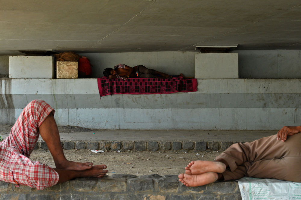 Indian men sleep in the shade under a bridge in New Delhi on May 27, 2015. More than 1,100 people have died in a blistering heatwave sweeping India, authorities said May 27, 2015, as forecasters warned searing temperatures would continue. AFP PHOTO / Chandan KHANNA