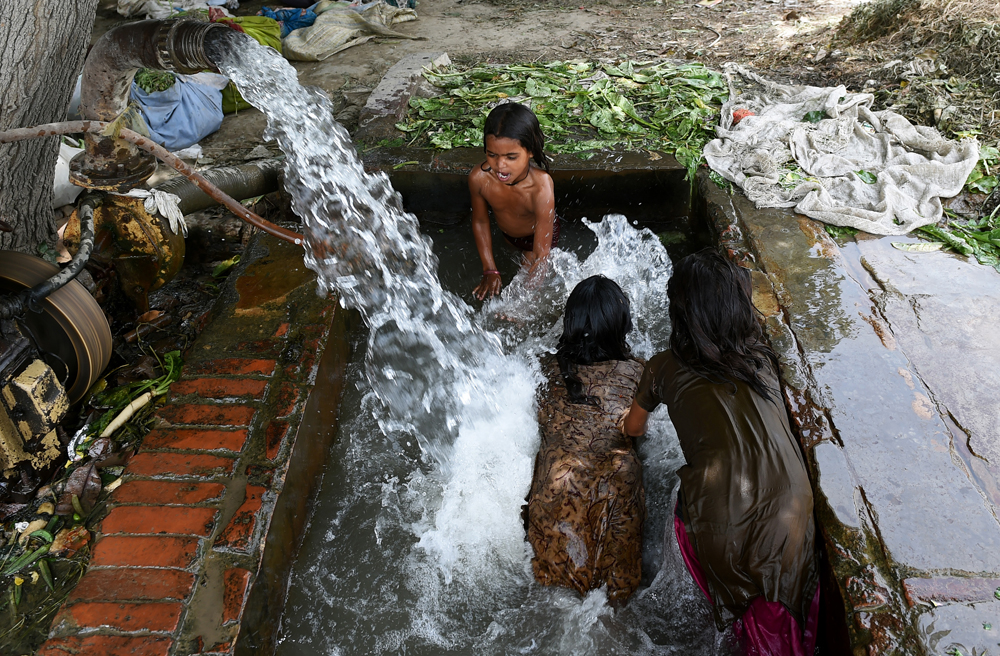 Indian children bathe in a tubewell on the outskirts of New Delhi on May 28, 2015. More than 1,100 people have died in a blistering heatwave sweeping India, authorities said, as forecasters warned searing temperatures would continue. AFP PHOTO/MONEY SHARMA