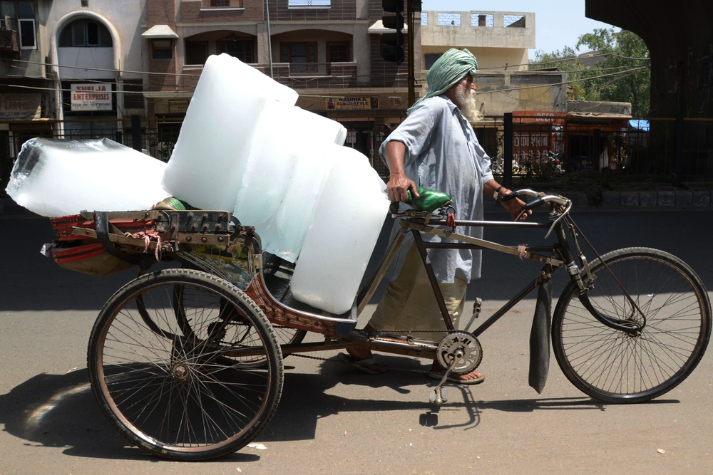 TOPSHOTS An Indian worker uses a ricksahw to transport ice from an ice factory in Amritsar on May 27, 2015.  More than 1,100 people have died in a blistering heatwave sweeping India, authorities said May 27, 2015, as forecasters warned searing temperatures would continue. AFP PHOTO/NARINDER NANU