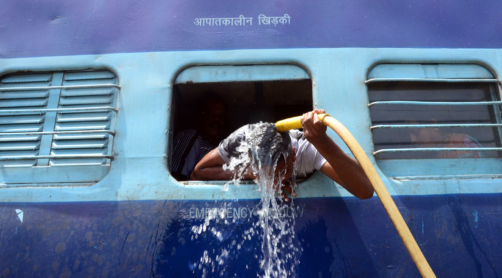 ALLAHABAD, INDIA - 2015/05/24: An Indian commuter uses the train water pipes  to bath  at railway station in Allahabad. Most of north India has been reeling under heat wave conditions with temperature soaring to over 46 degree Celsius (115 degrees Fahrenheit) . (Photo by Prabhat Kumar Verma/Pacific Press/LightRocket via Getty Images)