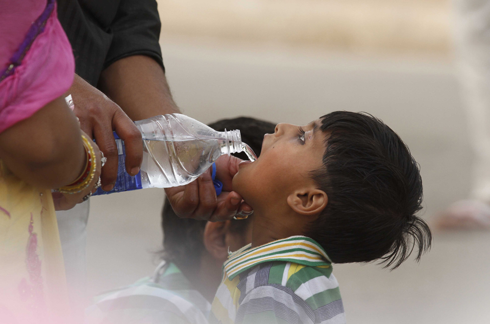NEW DELHI, INDIA - MAY 24: A boy drinking water from a bottle during a hot weather as Delhi/NCR experienced yet another scorching day, on May 24, 2015 in New Delhi, India. The national capital sizzling today as heat wave-like conditions prevailed across the city with mercury hovering above 44.7 degree Celsius, making life tough for the Delhiites. (Photo by Virendra Singh Gosain/Hindustan Times via Getty Images)