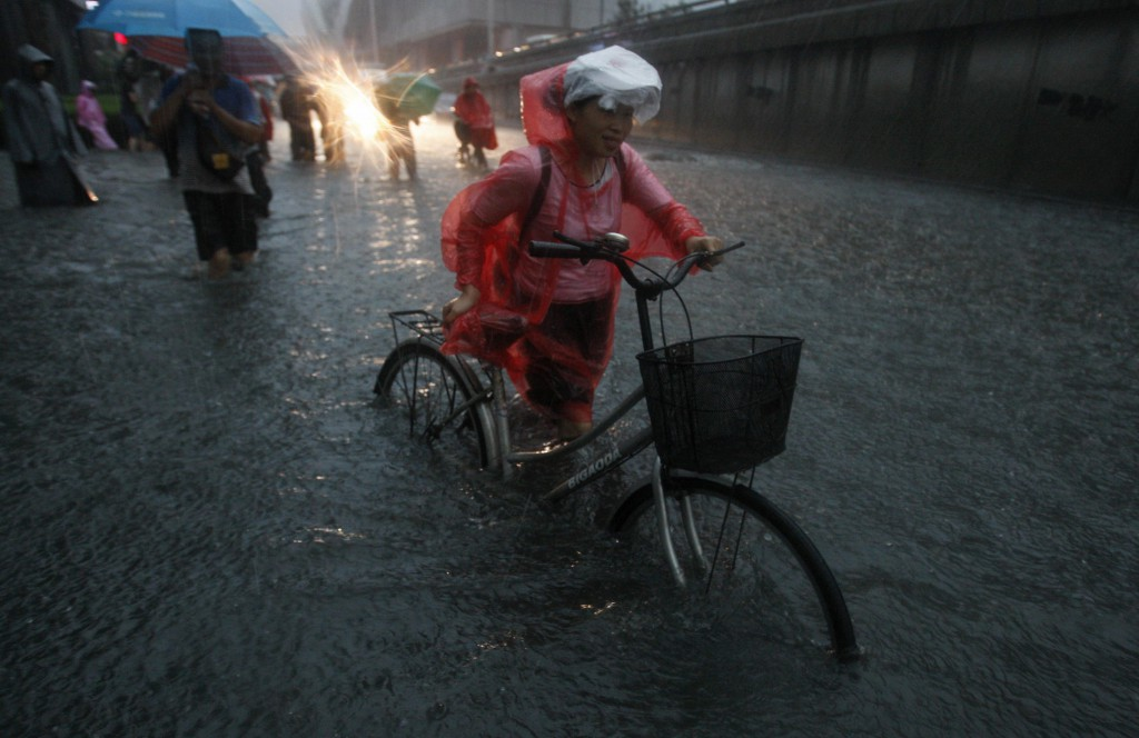 A resident pushes her bicycle on a flooded street amid heavy rainfalls in Beijing July 21, 2012. At least two people died and six others injured after a torrential thunderstorm hit Beijing on Saturday morning, inundating roads and cutting off traffic, police said. China's top meteorological authority said that rainstorms are expected to continue into the night, Xinhua News Agency reported. REUTERS/China Daily (CHINA - Tags: DISASTER ENVIRONMENT TPX IMAGES OF THE DAY) CHINA OUT. NO COMMERCIAL OR EDITORIAL SALES IN CHINA