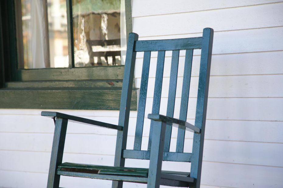 close-up-of-wooden-rocking-chair-on-house-front-porch