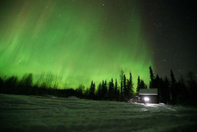 SKWENTNA, ALASKA.- The Northern Lights illuminate the night sky over Roger and Myra's Skwentna homestead. (Photo Credit: © National Geographic Channels/ Peter Bobrow)