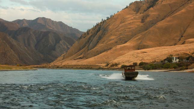 HELLS CANYON, IDAHO- Brice's boat traveling on the Snake River beside the mountains of Hells Canyon. (Photo Credit: © National Geographic Channels/ Peter Bobrow)