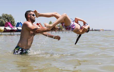 Keszthely, 2015. június 5. Egy férfi kislányával a Balatonban a keszthelyi strandon 2015. június 5-én. MTI Fotó: Varga György