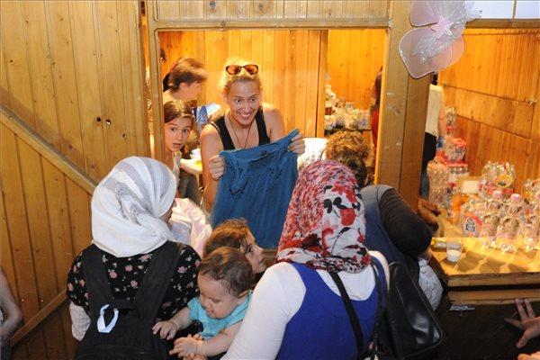 Szeged, 2015. július 2.  Önkéntesek ételt, italt és ruhát osztanak 2015. július 1-jén a szegedi pályaudvar előtt felállított faházban azoknak a bevándorlóknak, akik nem érték el az utolsó, Budapestre induló vonatot. MTI Fotó: Kelemen