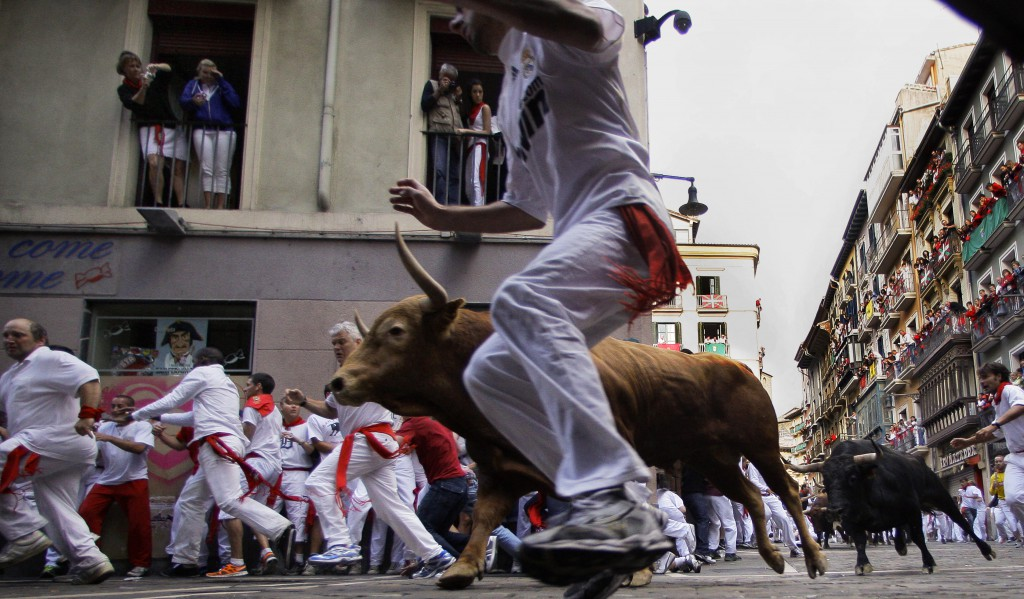 Revelers run on Estafeta corner with Torrehandilla's fighting bulls ranch, during the eighth and last running of the bulls at the San Fermin fiestas, in Pamplona northern Spain, Saturday, July 14, 2012. (AP Photo/Alvaro Barrientos)