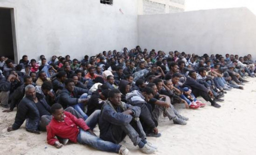 1290-193380_a_group_of_irregular_migrants_who_had_been_heading_for_europe_wait_after_being_detained_by_libyan_coastguards
