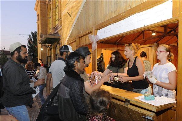 Szeged, 2015. július 2.  Önkéntesek ételt és italt osztanak 2015. július 1-jén a szegedi pályaudvar előtt felállított faházban azoknak a bevándorlóknak, akik nem érték el az utolsó, Budapestre induló vonatot.  MTI Fotó: Kelemen Zoltán Gergely