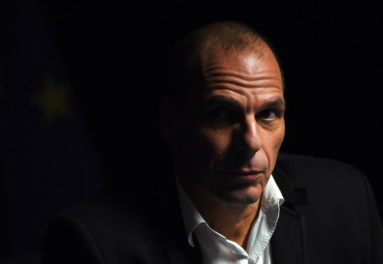 Greek Finance Minister Yanis Varoufakis holds a press conference, as an attendee turned of the lights, after an Eurogroup finance ministers meeting at the European Council headquarters in Brussels, February 20, 2015. Greece will prioritise EU-acceptable reforms, a government source said after eurozone finance ministers granted Athens a four-month loan extension. AFP PHOTO/Emmanuel Dunand