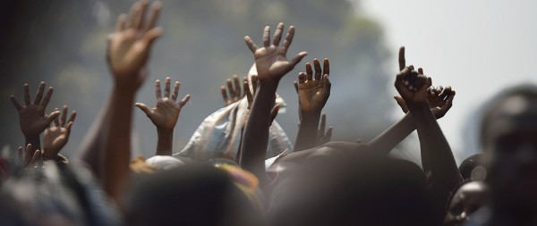 TOPSHOTS Displaced people raise their hands as they wait for food distribution, near Mpoko Bangui's airport where 100.000 people have found shelter on January 8, 2014.<div class='article-ad'><script src=