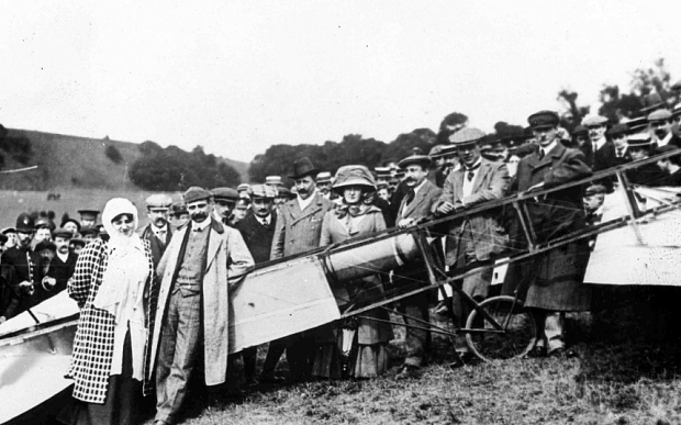 Louis Bleriot, Alicia Bleriot...FILE -- This Sunday, July 25, 1909 file photo shows French pilot Louis Bleriot, second left, with his wife Alicia, left, surrounded by well wishers after landing on a golf course near Dover, England. The flight came six years after the Wright brothers flew overland over Kitty Hawk, North Carolina, and during a decade in which pioneers in Europe and North America were developing the rudiments of airplane technology and expanding its limits.  (AP Photo/file)