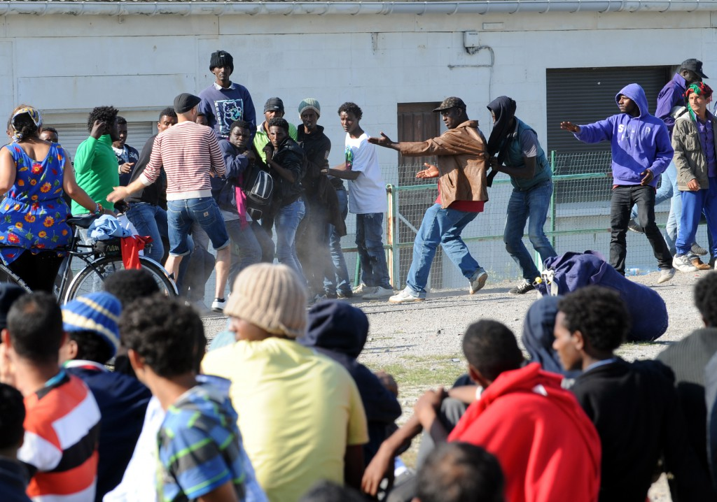 Migrants clash together during a food distribution in Calais, northern France, on August 5, 2014. Dozens were hurt on the early hours after clashes broke out in the port of Calais between hundreds of African migrants seeking to cross the Channel to England.  Police reinforcements were called to break up fights between groups of mainly Eritrean and Sudanese migrants that left 51 people hurt, one of whom was sent by helicopter to hospital with serious head injuries.  AFP PHOTO / FRANCOIS LO PRESTI