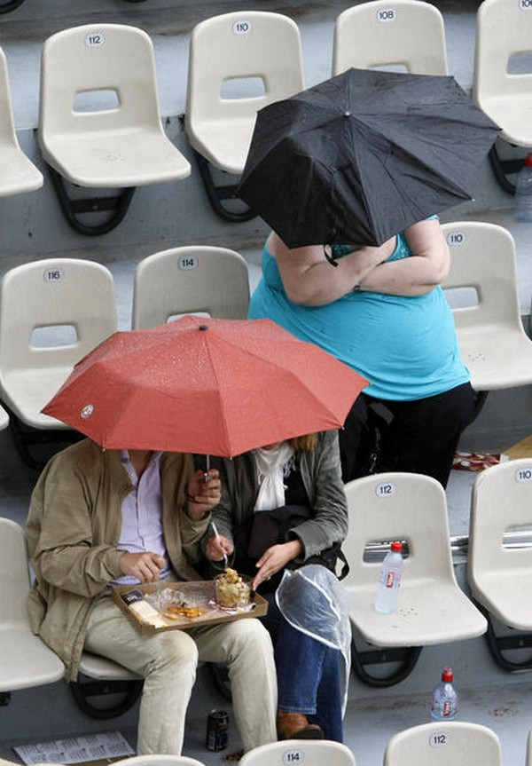 Fans protect themselves from the rain under umbrellas during France's Nicolas Devilder's match against Spain's Rafael Nadal at the French Open tennis tournament at Roland Garros in Paris May 29, 2008. REUTERS/Francois Lenoir (FRANCE)