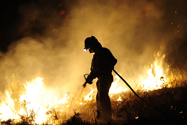 A member of the fire brigade of Belchite works around a fire in Andorra early on July 23, 2009, near Teruel.  Some 500 people were battling on July 22 a wind-fuelled wildfire in northeastern Spain which claimed the lives of four firefighters and seriously injured two others, Defence Minister Carme Chacon said.    AFP PHOTO / Pedro ARMESTRE