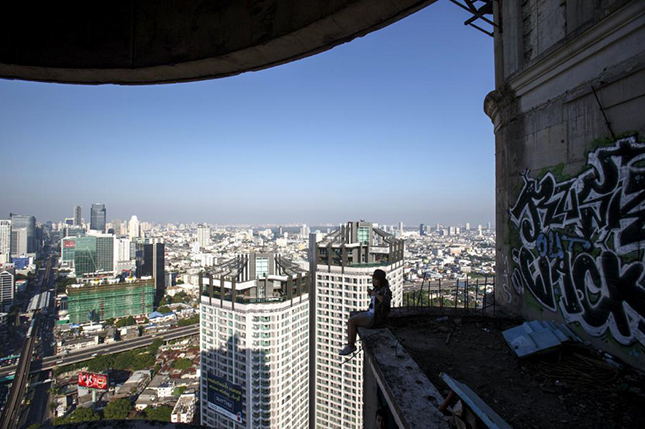 A visitor sits on a balcony of an abandoned building in Bangkok April 19, 2015. The abandoned building, known as Sathorn Unique, dubbed the 'ghost tower' was destined to become one of Bangkok's most luxurious residential addresses but construction was never completed as the Thai economy was hit during the 1997 Asian Financial Crisis. Now, many travellers visit and explore the 49-storey skyscraper. REUTERS/Athit Perawongmetha