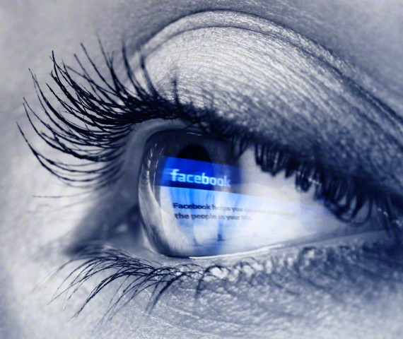 Closeup of a young woman blue eye with Facebook logo reflecting in it.<div class='article-ad'><script src=