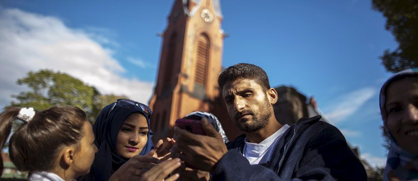 Ihab, 30, (R) a Syrian migrant from Deir al Zor, shows photographs to his sister Sara, 19, on his mobile phone before surrending to the police to apply for asylum after he spent two days with his family in Lubeck, Germany September 20, 2015.<div class='article-ad'><script src=