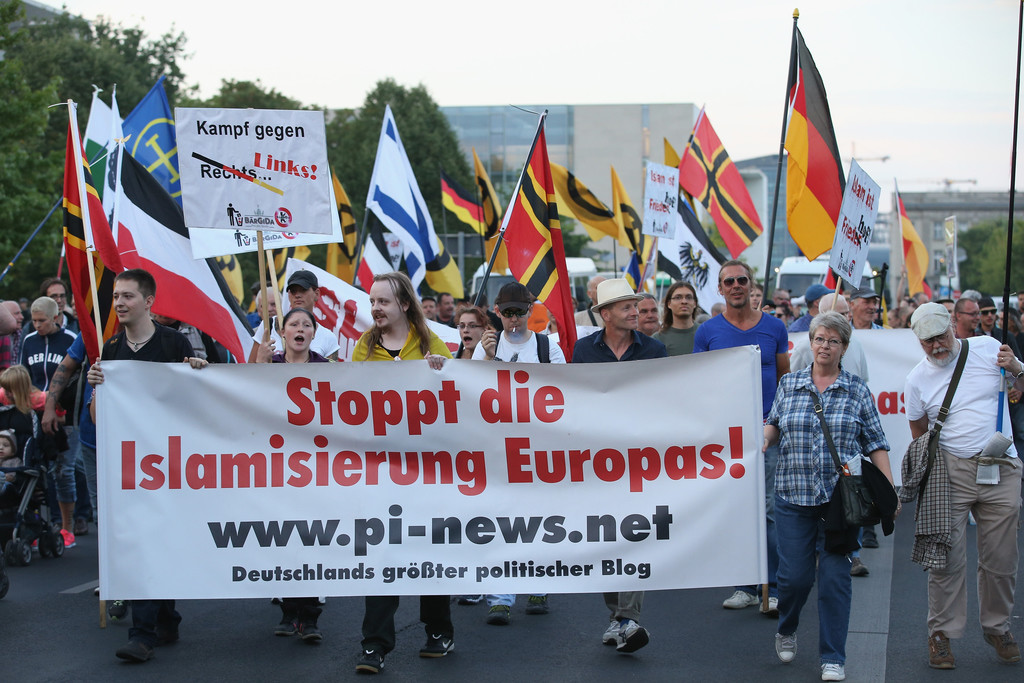 "BERLIN, GERMANY - AUGUST 24:  Supporters of the Pegida movement carry a banner that reads: ""Stop the Islamization of Europe"" as they march past the Chancellery (behind) on August 24, 2015 in Berlin, Germany. Pegida is critical of Islam and many of its supporters see Muslim immigration as a threat to Germany. Germany is expected to take in 800,000 refugees and migrants this year, many of them from Muslim countries such as Syria, Afghanistan and Iraq, and Germany has seen a spate of protests and violence in recent weeks by right-wing supporters opposing the influx of aslyum-seekers.  (Photo by Sean Gallup/Getty Images)"