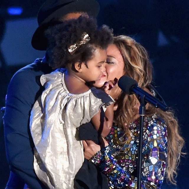INGLEWOOD, CA - AUGUST 24: Recording artist Jay Z (behind, wearing hat) and daughter Blue Ivy Carter (C) present the Michael Jackson Video Vanguard Award to honoree Beyonce (R) onstage during the 2014 MTV Video Music Awards at The Forum on August 24, 2014 in Inglewood, California. Michael Buckner/Getty Images/AFP