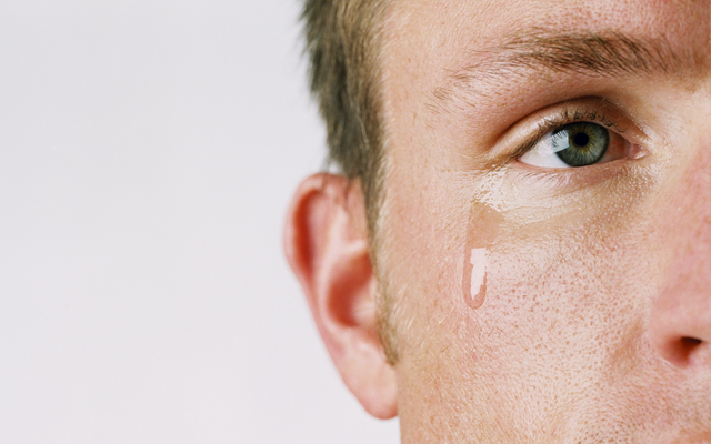 close-up of the side of a man's face with a tear coming out of his eye