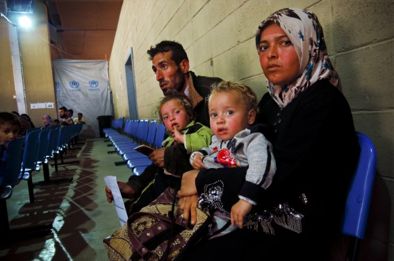 "Um Ahmed, her husband Abu Ahmed, and their two children sit inside a United Nations refugee registration center in Tripoli, Lebanon. They fled the northern Syrian city of Aleppo a month ago. ""There was a lot of shelling,"" said Um Ahmed, ""I wasn't thinking, I was just thinking of my children."""