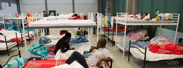 Flüchtlinge aus verschiedenen Ländern sitzen und liegen am 30.06.2014 im Erstaufnahmelager der Bayernkaserne in München (Bayern) in den Betten ihrer Unterkunft, die in einer ehemaligen Bundeswehr-LKW-Garage eingerichtet wurde. In Bayern werden dieses Jahr etwa 30 000 neue Asylbewerber erwartet. Im Jahr 2013 hatte der Freistaat 17 000 Flüchtlinge aufgenommen. Foto: Peter Kneffel/dpa +++(c) dpa - Bildfunk+++