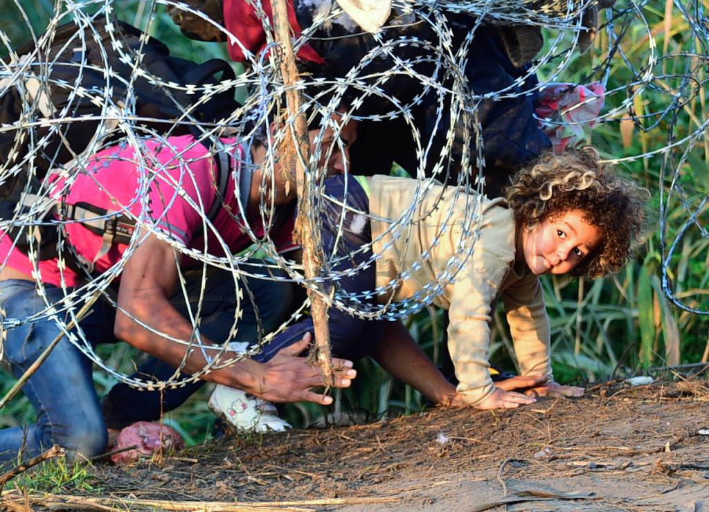 Asszonyoktól elvett gyermekekkel mennek át a drótakadályokon az országhatárokon a férfiak