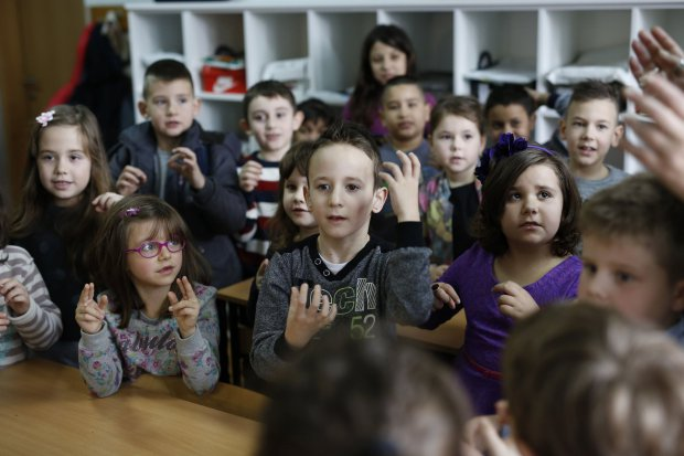 In this photo taken Thursday, Feb. 4, 2016, Bosnian boy Zejd Coralic, center, learns sign language from teacher Anisa Setkic-Sendic, not shown, with other children in a class at an elementary school in Sarajevo, Bosnia. In 2003, Bosnia adopted laws that allow children with disabilities to be fully integrated into society, including schools. Children with special needs are supposed to have professional assistants who sit with them in class, translating or otherwise helping them participate. But in practice, impoverished Bosnia barely has enough money to keep normal schools functioning and children with disabilities are left to the care and imagination of their parents and the good will of school staff. (AP Photo/Amel Emric)