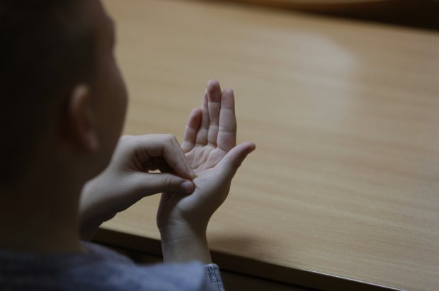 In this photo taken Thursday, Feb. 4, 2016, Bosnian boy Zejd Coralic learns sign language from teacher Anisa Setkic-Sendic in a class at an elementary school in Sarajevo, Bosnia. In 2003, Bosnia adopted laws that allow children with disabilities to be fully integrated into society, including schools. Children with special needs are supposed to have professional assistants who sit with them in class, translating or otherwise helping them participate. But in practice, impoverished Bosnia barely has enough money to keep normal schools functioning and children with disabilities are left to the care and imagination of their parents and the good will of school staff. (AP Photo/Amel Emric)