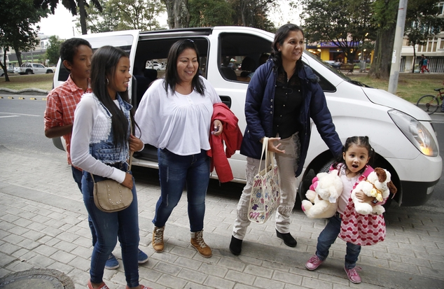 Jacqueline Vasquez Sanchez, third left, and her sister Lorena Sanchez walk with their children, before a press conference in Bogota, Colombia, Thursday, Feb. 25, 2016. The reunited sisters were separated more than 30 years ago, when on November 13, 1985, the Nevado del Ruiz volcano erupted triggering a deluge of mud and debris that buried the town of Armero, killing more than 25,000 people in and around the town. (AP Photo/Fernando Vergara)