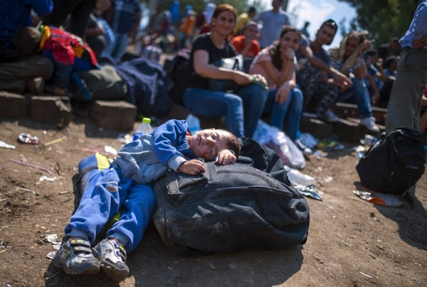 "A young boy sleeps on a duffel bag as migrants wait to cross the Macedonian-Greek border near the town of Gevgelija on August 20, 2015. Macedonia said on August 20 that it had declared a ""state of emergency"" on its southern border with Greece and would draft in the army to help control the influx of migrants crossing the frontier. AFP PHOTO / ROBERT ATANASOVSKI"