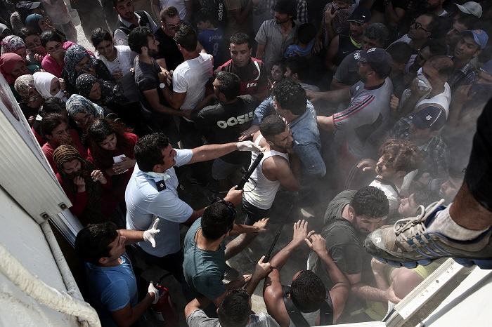 A policeman hits a migrant as police try to disperse hundreds of migrants, during a registration procedure which was taken place at the stadium of Kos town, on the southeastern island of Kos, Greece, Tuesday, Aug. 11, 2015. Fights broke out among migrants on the Greek island of Kos Tuesday, where overwhelmed authorities are struggling to contain increasing numbers of people arriving clandestinely on rubber dinghies from the nearby Turkish shore. (AP Photo/Yorgos Karahalis)