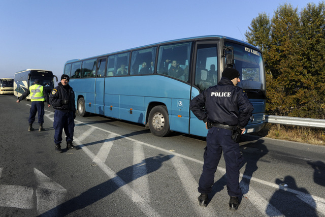 Greek police officers direct buses carrying hundreds of migrants, who were stranded on the Greek-Macedonian border and blocked rail traffic, after a police operation near the village of Idomeni