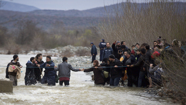 A woman is assisted while crossing the river along with other migrants, north of Idomeni, Greece, attempting to reach Macedonia on a route that would bypass the border fence, Monday, March 14, 2016. Hundreds of migrants and refugees walked out of an overcrowded camp on the Greek-Macedonian border Monday, determined to use a dangerous crossing to head north. (AP Photo/Visar Kryeziu)