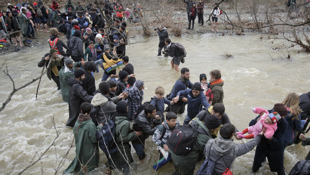 A baby is passed from hand to hand as migrants cross a river, north of Idomeni, Greece, attempting to reach Macedonia on a route that would bypass the border fence, Monday, March 14, 2016. Hundreds of migrants and refugees walked out of an overcrowded camp on the Greek-Macedonian border Monday, determined to use a dangerous crossing to head north. (AP Photo/Vadim Ghirda)