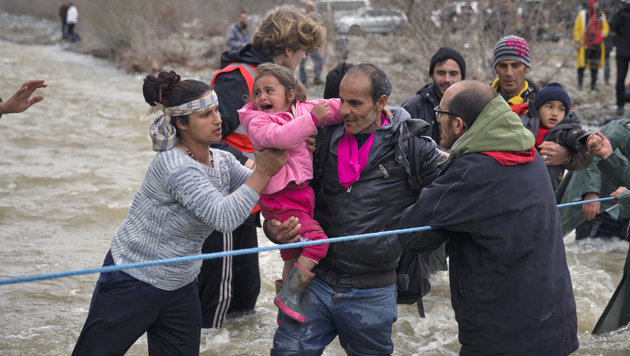 A girl cries as migrants cross a river, north of Idomeni, Greece, attempting to reach Macedonia on a route that would bypass the border fence, Monday, March 14, 2016. Hundreds of migrants and refugees walked out of an overcrowded camp on the Greek-Macedonian border Monday, determined to use a dangerous crossing to head north.(AP Photo/Vadim Ghirda)