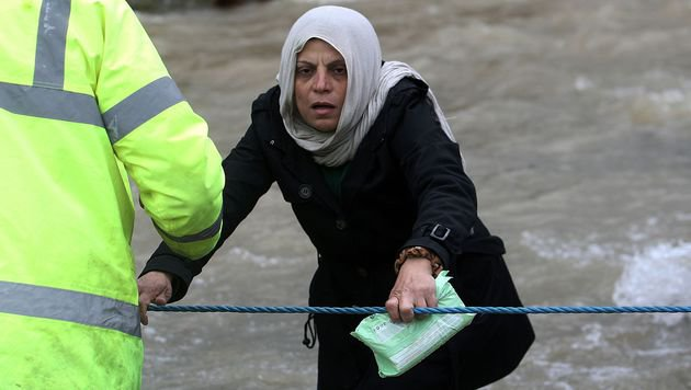 A woman reacts as migrants and refugees cross a river on their way to Macedonia from a makeshift camp at the Greek-Macedonian border near the Greek village of Idomeni where thousands of them are stranded by the Balkan border blockade on March 14, 2016. Hundreds of desperate migrants were stopped by Macedonian troops after wading thigh-deep through a surging river to cross the border from Greece, where thousands have been left stranded after Balkan states slammed Europe's migrant door shut. / AFP PHOTO / SAKIS MITROLIDIS