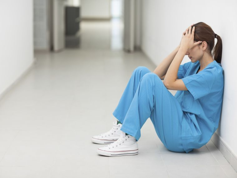 Nurse sitting in a corridor while holding her head