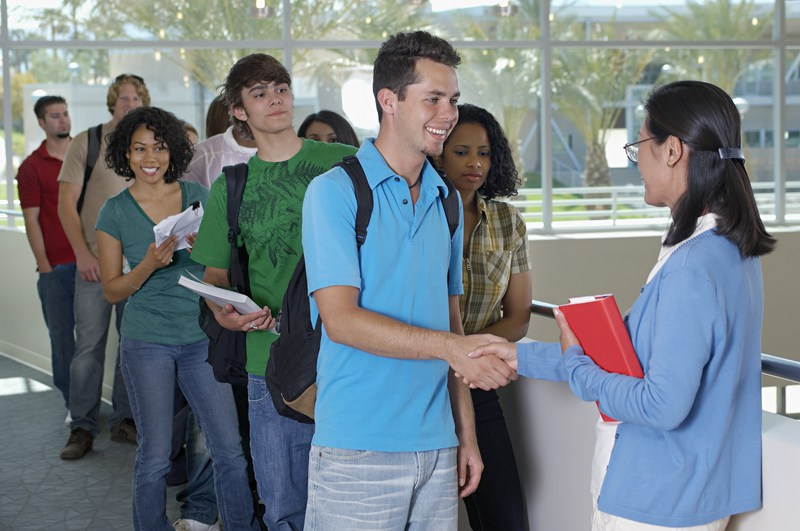 Male-student-shaking-hands-with-teacher