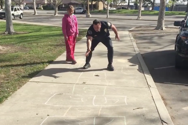 Police-officer-teaches-homeless-girl-how-to-play-hopscotch (2)