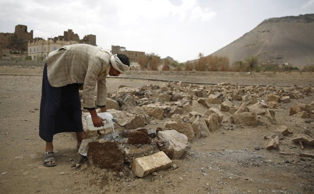 In this Monday, March 28, 2016 photo, Faisal Ahmed, whose son, Udai Faisal, died of severe acute malnutrition, pours water on his grave in Hazyaz village on the southern outskirts of Sanaa, Yemen. Hunger has been the most horrific consequence of Yemenís conflict and has spiraled since Saudi Arabia and its allies, backed by the U.S., launched a campaign of airstrikes and a naval blockade a year ago. (AP Photo/Hani Mohammed)